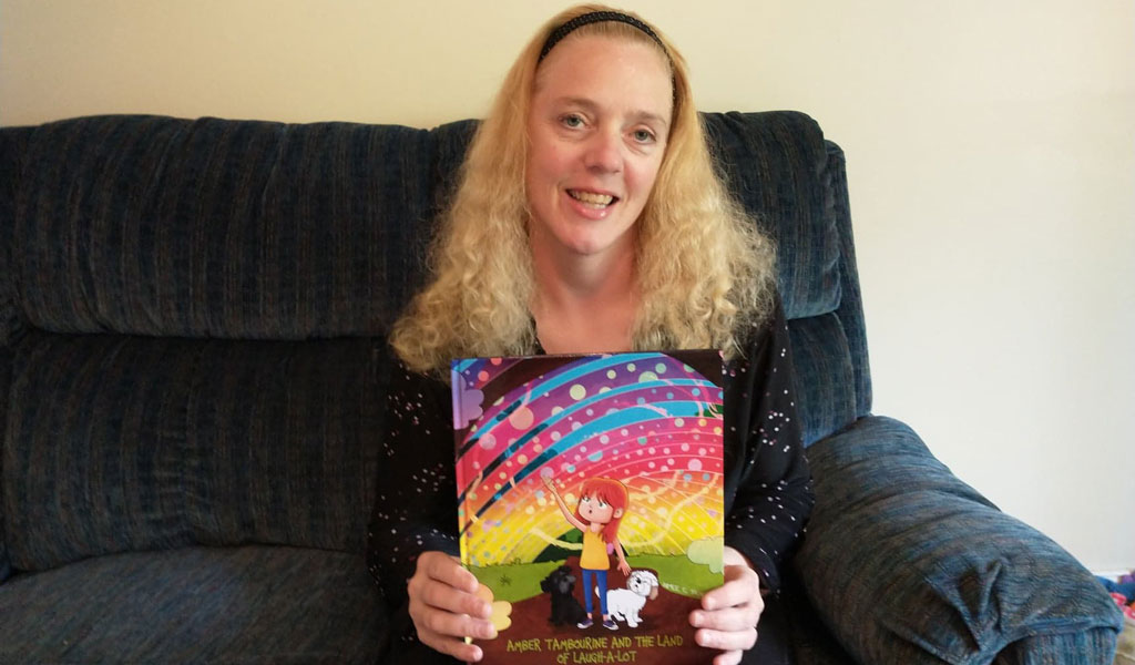 Aimee C. Trafton with her book, Amber Tambourine and the Land of Laugh-a-Lot.