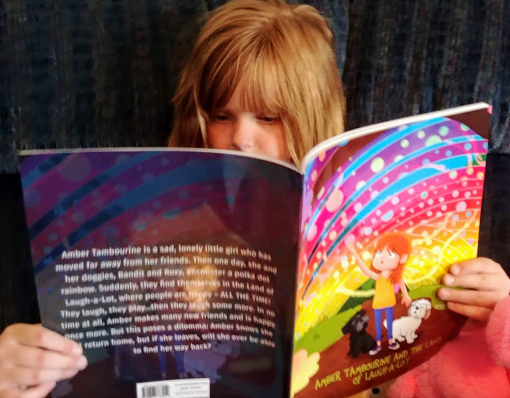 Child reading Aimee C. Trafton's book Amber Tambourine and the Land of Laugh-a-Lot.