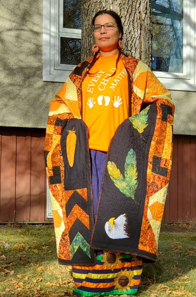 Jessie Wãpos draped in a quilt that was gifted to her.
